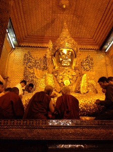Monks applying gold leaf to the image of Buddha in Mandalay