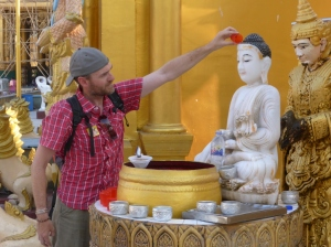 Dean pouring water over the Buddha image for his birth day of the week