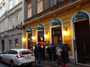 People lining up on a rainy night in Vienna